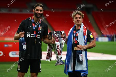 Jordan Turnbull and Sam Hoskins of Northampton Town celebrate with the trophy after their team beat Exeter 4-0 the Sky Bet League 2 Play off Final