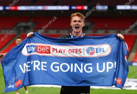 Callum Morton of Northampton Town celebrates with a 'We're Going Up' flag after his team beat Exeter 4-0 the Sky Bet League 2 Play off Final