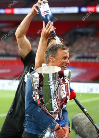 Northampton Town manager Keith Curle has Champagne poured over his head as he carries the trophy after his team beat Exeter 4-0 the Sky Bet League 2 Play off Final