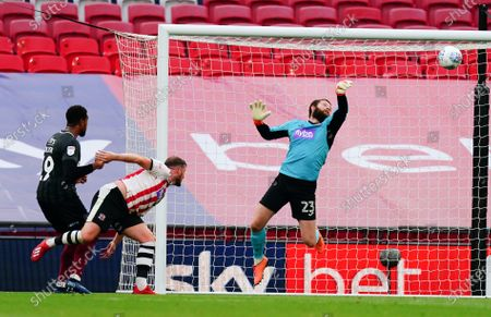 Exeter City goalkeeper Jonathan Maxted makes a save on the goal line after a shot from Vadaine Oliver of Northampton Town