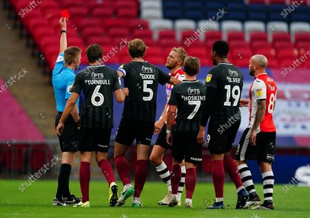 As Northampton players surround the referee, Dean Moxey of Exeter City is shown a red card by Michael Salisbury