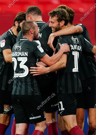 Northampton Town players celebrate with Andy Williams after he scores the fourth goal to secure promotion during the Sky Bet League 2 Play off Final between Exeter City and Northampton Town