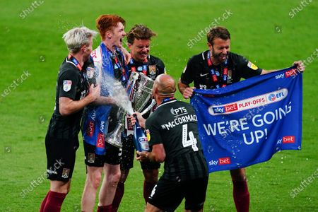 Northampton goalscorers Callum Morton, Ryan Watson, Sam Hoskins and Andy Williams gets sprayed by Alan McCormack as they secure promotion to League One after beating Exeter City in the Sky Bet Play off final