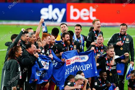 Northampton Town celebrate, with Sky Bet branding, after securing promotion to League One after beating Exeter City in the Sky Bet Play off final