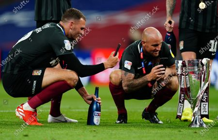 Harry Smith and Alan McCormack of Northampton Town celebrate on the pitch with the trophy after beating Exeter City 4-0 in the Sky Bet League Two Play off Final and securing promotion to League One.