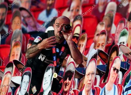 Alan McCormack of Northampton Town celebrates with a beer and the fan cardboard cutouts after the 4-0 final win