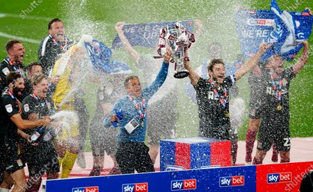 Northampton Town manager Keith Curle and Charlie Goode lift the trophy after their play off final win