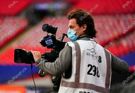 A television cameraman wearing a protective mask