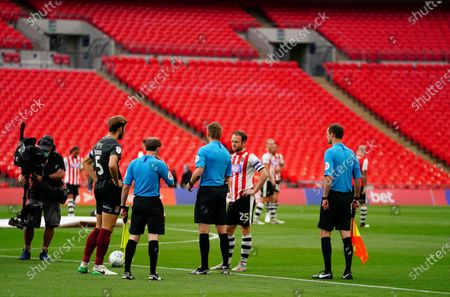 The referee performs the coin toss