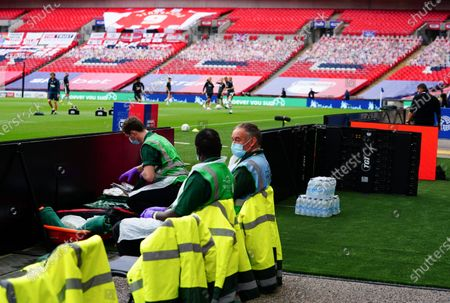 Medical staff sit at the edge of the pitch wearing PPE before the start of the SkyBet League 2 play off final between Exeter City and Northampton Town