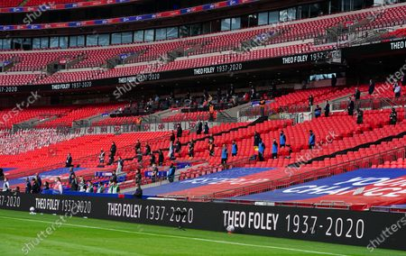 Staff members in the stands from both teams stand for a minute's silence for Theo Foley before the start of the Sky Bet League 2 Play off Final between Exeter City and Northampton Town