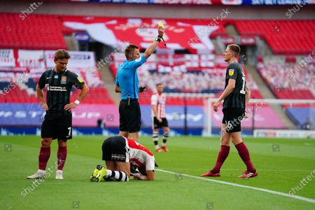 Scott Wharton of Northampton Town receives a yellow card early on in the game for fouling Randell Williams of Exeter City