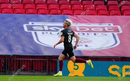 Ryan Watson of Northampton Town celebrates scoring the opening goal, in front of Sky Bet branding, during the League 2 Play Off final
