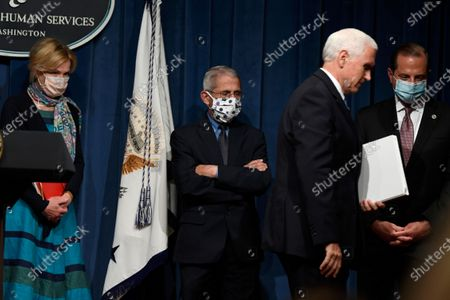 Stock Image of Vice President Mike Pence, second from right, walks off of the stage following the conclusion of a briefing with the Coronavirus Task Force at the Department of Health and Human Services in Washington. Dr. Deborah Birx, left, Dr. Anthony Fauci, second from left, and Health and Human Services Secretary Alex Azar, right, follow Pence. On Friday, Pence said Americans should look to their state and local leadership for modeling their behavior. The comments only days after President Donald Trump held two campaign events that drew hundreds of participants but few wearing masks