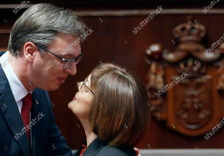 Serbian President Aleksandar Vucic, left, kisses Maja Gojkovic, the speaker of Serbia's parliament during an inauguration ceremony, in Belgrade, Serbia. Gojkovic has tested positive with the coronavirus. Serbia has seen a spike in coronavirus cases since lifting strict lockdown measures in May, allowing large gathering without obligatory social distancing or wearing masks