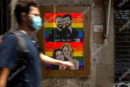 A man walks past the new work of street artist Tvboy depicting leader of People's Party Pablo Casado (R-top), leader of extreme right wing party Vox, Santiago Abascal (L-top), PP's spokeswoman at Parliament, Cayetana Alvarez de Toledo (R-bottom), and spokeswoman of Ciudadanos Party, Ines Arrimadas (L-bottom) in Barcelona, Spain, 27 June 2020.