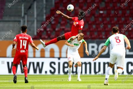 Leipzig's Ibrahima Konate, top, and Augsburg's Alfred Finnbogason challenge for the ball during the German Bundesliga soccer match between FC Augsburg and RB Leipzig in Augsburg, Germany