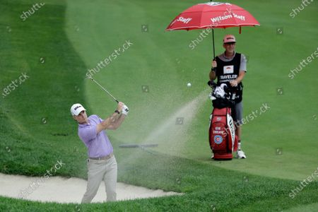 Kevin Streelman hits out of a sand trap on the 15th hole during the third round of the Travelers Championship golf tournament at TPC River Highlands, in Cromwell, Conn