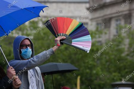 A demonstrator holds up a fan at a Trans rights march in Manchester.