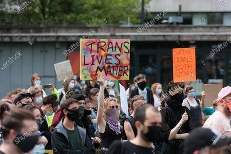Trans rights advocates hold up signs in Manchester.
