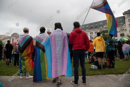 People draped in flags at a Trans rights march in Manchester.
