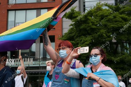 People hold up flags at a Trans rights march in Manchester.