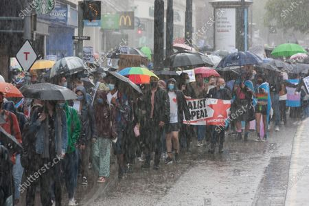 Demonstrators march through terrible weather at a Trans rights march in Manchester.