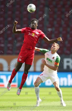 Ibrahima Konate (L) of Red Bull Leipzig is challenged by Alfred Finnbogason of FC Augsburg during the German Bundesliga soccer match between FC Augsburg and RB Leipzig at WWK-Arena in Augsburg, Germany, 27 June 2020.