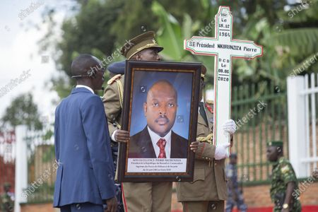 Stock Image of A military officer holds a portrait of late Burundian President Pierre Nkurunziza during his funeral in Gitega, Burundi, June 26, 2020. Late Burundian President Pierre Nkurunziza, who died in office of heart attack on June 8, was laid to rest on Friday at a state funeral in political capital Gitega, central Burundi.