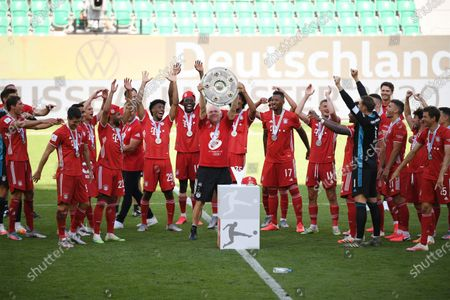 Assistant coach Hermann Gerland of FC Bayern Munich lifts the trophy to celebrate the championship following the Bundesliga match between VfL Wolfsburg and FC Bayern Muenchen at Volkswagen Arena on June 27, 2020 in Wolfsburg, Germany.