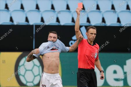 Referee Guillermo Cuadra, right, shows a red card to Celta Vigo's Iago Aspas after scored his side's second goal during a Spanish La Liga soccer match between RC Celta and Barcelona at the Balaidos stadium in Vigo, Spain