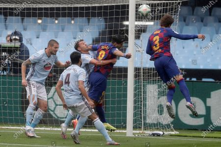 Barcelona's Gerard Pique, right, heads for the ball during a Spanish La Liga soccer match between RC Celta and Barcelona at the Balaidos stadium in Vigo, Spain