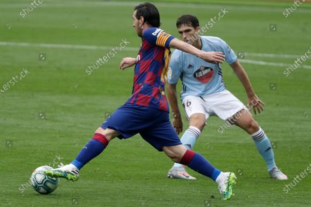 Barcelona's Lionel Messi, left, vies for the ball with Celta Vigo's Jorge Saenz during a Spanish La Liga soccer match between RC Celta and Barcelona at the Balaidos stadium in Vigo, Spain