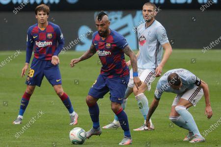 Barcelona's Arturo Vidal, center, controls the ball during a Spanish La Liga soccer match between RC Celta and Barcelona at the Balaidos stadium in Vigo, Spain