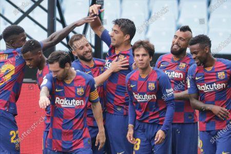 Barcelona's Luis Suarez, center, celebrates after scoring the opening goal during a Spanish La Liga soccer match between RC Celta and Barcelona at the Balaidos stadium in Vigo, Spain