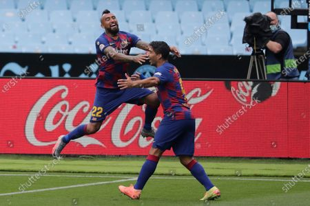 Barcelona's Luis Suarez, right, celebrates after with his teammate Barcelona's Arturo Vidal after scoring the opening goal during a Spanish La Liga soccer match between RC Celta and Barcelona at the Balaidos stadium in Vigo, Spain