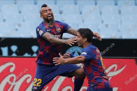 Barcelona's Luis Suarez, right, celebrates after with his teammate Barcelona's Arturo Vidal the opening goal during a Spanish La Liga soccer match between RC Celta and Barcelona at the Balaidos stadium in Vigo, Spain
