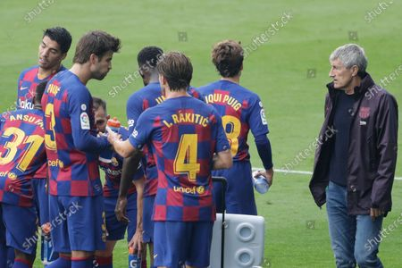 Barcelona's head coach Quique Setien, right, stands next to his players during a Spanish La Liga soccer match between RC Celta and Barcelona at the Balaidos stadium in Vigo, Spain