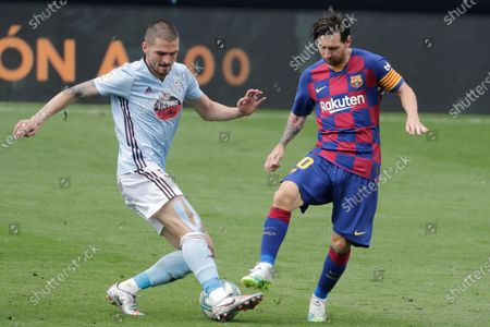Barcelona's Lionel Messi, right, fights for the ball with Celta Vigo's Okay Yokuslu during a Spanish La Liga soccer match between RC Celta and Barcelona at the Balaidos stadium in Vigo, Spain