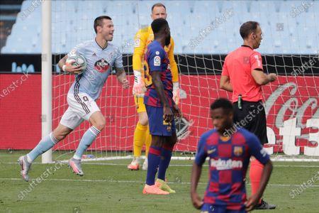 Celta Vigo's Smolov, left, celebrates after scoring his side's first goal during a Spanish La Liga soccer match between RC Celta and Barcelona at the Balaidos stadium in Vigo, Spain