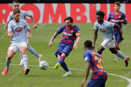 Barcelona's Lionel Messi, center, kicks the ball during a Spanish La Liga soccer match between RC Celta and Barcelona at the Balaidos stadium in Vigo, Spain