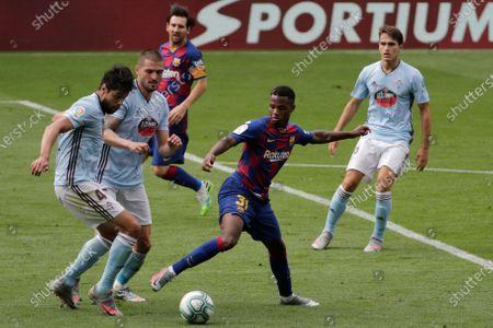 Barcelona's Ansu Fati, second right, duels for the ball with Celta Vigo's Nestor Araujo during a Spanish La Liga soccer match between RC Celta and Barcelona at the Balaidos stadium in Vigo, Spain