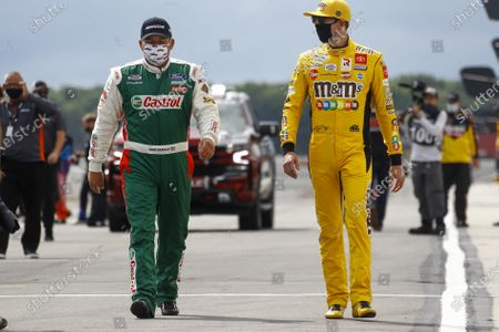 Ryan Newman, left and Kurt Busch walk down pit row down before the start of a scheduled NASCAR Cup Series auto race at Pocono Raceway, in Long Pond, Pa