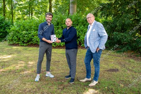 Former Dutch international Mark van Bommel (L) hands over the first copy of the book Sneijder to national team record holder Wesley Sneijder. Journalist Kees Jansma (R) wrote the biography about the life of the former soccer player.