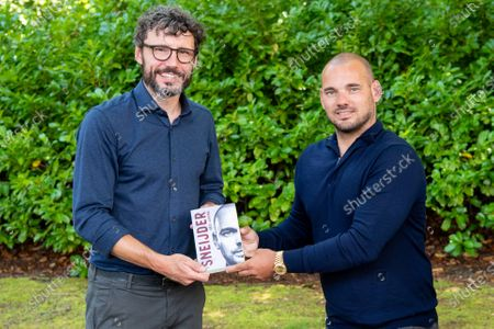 Former Dutch international Mark van Bommel (L) hands over the first copy of the book Sneijder to national team record holder Wesley Sneijder.