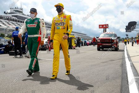 Drivers Ryan Newman, left and Kurt Busch walk down pit row down before the start of the NASCAR Cup Series auto race at Pocono Raceway, in Long Pond, Pa