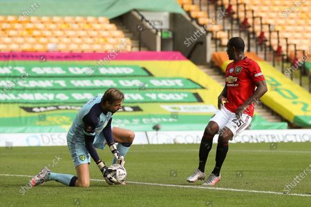 Odion Ighalo (R) of Manchester United in action against Norwich goalkeeper Tim Krul (L) during the English FA Cup quarter final soccer match between Norwich City and Manchester United in Norwich, Britain, 27 June 2020.