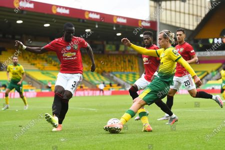 Todd Cantwell (2-R) of Norwich in action against Eric Bailly (L) of Manchester United during the English FA Cup quarter final soccer match between Norwich City and Manchester United in Norwich, Britain, 27 June 2020.