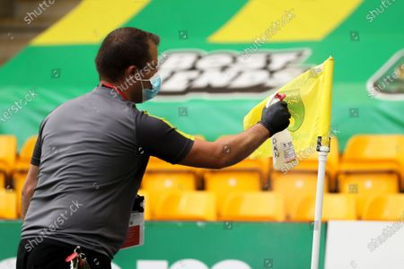 A staff member disinfects a corner flag during the English FA Cup quarter final soccer match between Norwich City and Manchester United in Norwich, Britain, 27 June 2020.