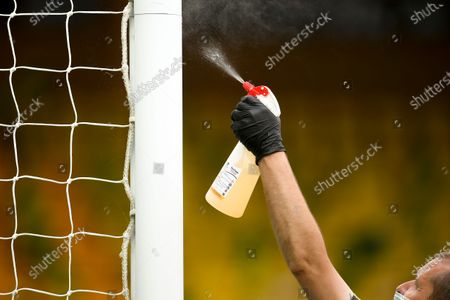 A staff member disinfects the goal post during the English FA Cup quarter final soccer match between Norwich City and Manchester United in Norwich, Britain, 27 June 2020.